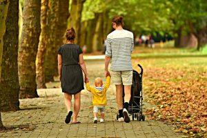Junges Paar läuft durch den Park mit ihrem Kind an der Hand