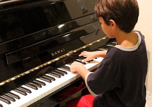 Kind am Piano sitzend